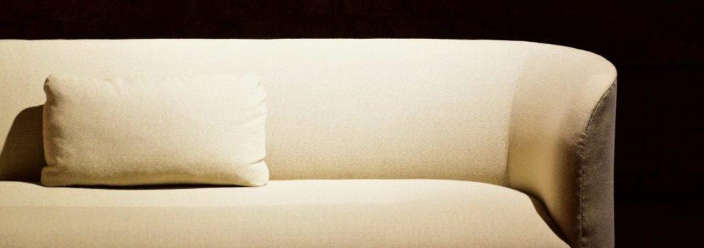 Halbrundes Sofa vor schwarzer Wand